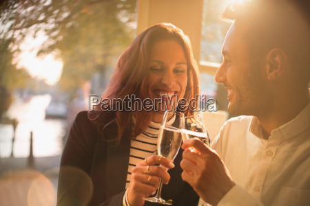 smiling romantic couple toasting champagne glasses
