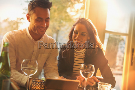 young couple drinking wine and using