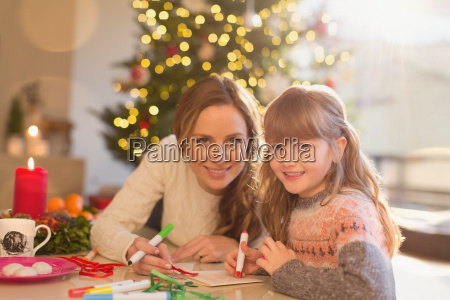portrait smiling mother and daughter coloring