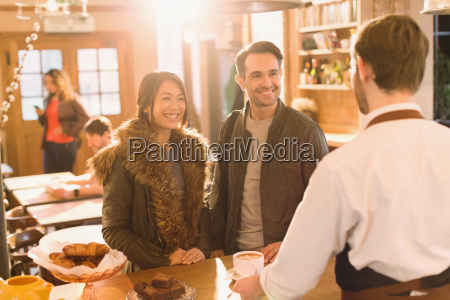 barista serving coffee to couple at
