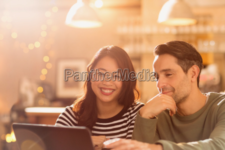 smiling couple video chatting at laptop