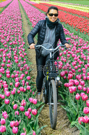 young woman biking through tulip fields