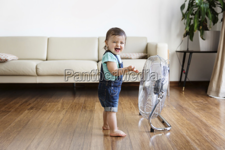 young boy wearing denim dungarees standing