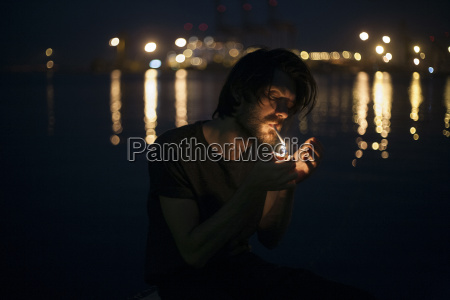 caucasian man lighting cigarette at waterfront