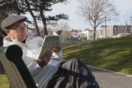 hispanic man sitting on park bench